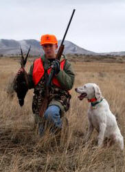 Hunter with bird and dog. Photo by Harry Morse.